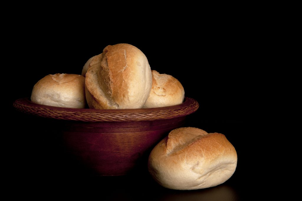 Freshly baked buns in a wooden bowl.
