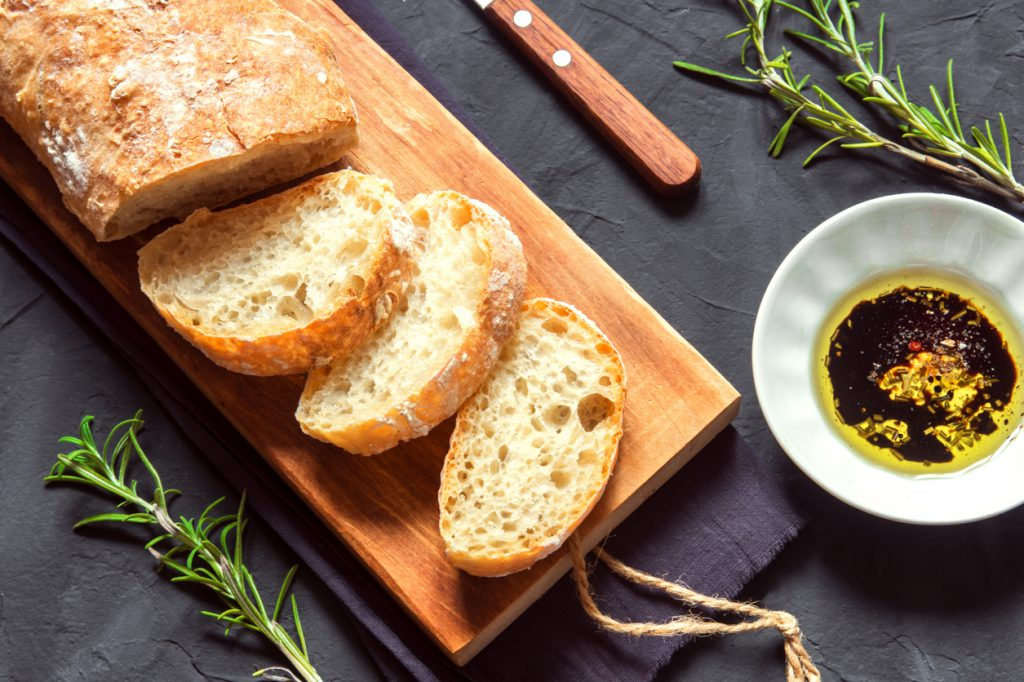 Italian bread Ciabatta with olive oil and rosemary on black background - fresh