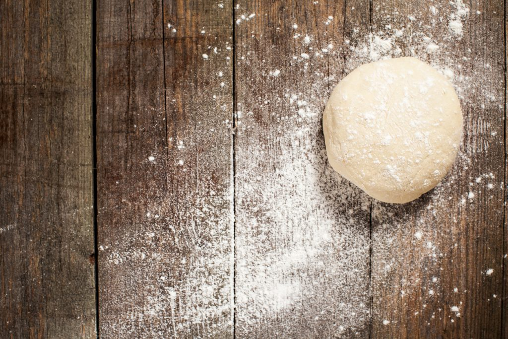 Traditional pizza dough, proved and ready to be made into a delicious stone baked pizza. On a rustic textured wooden background, dusted with flour
