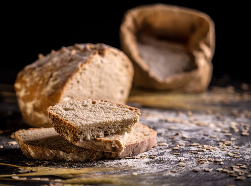 Sourdough bread, sliced on black background