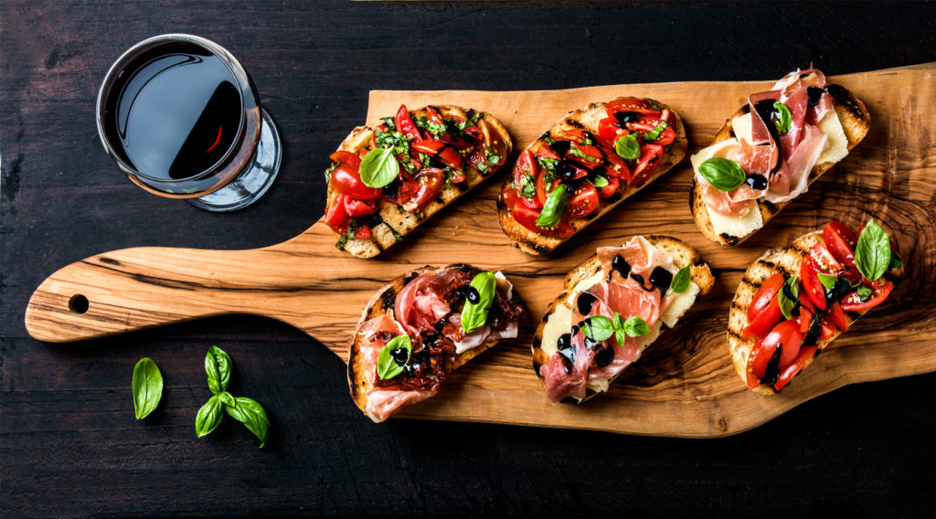 Brushetta set for wine. Variety of small saBruschetta sandwiches with prosciutto, tomatoes, parmesan cheese, fresh basil and balsamic creme served with glass of red wine on rustic wooden board over dark background, top view