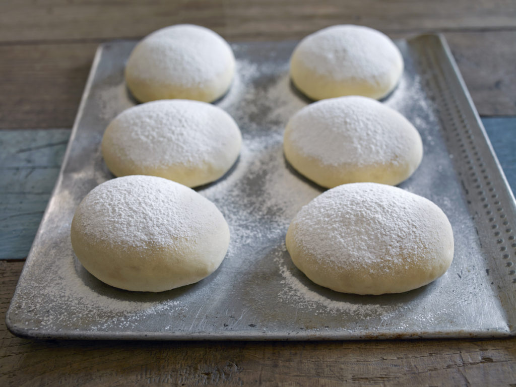 tray of bread dough balls on table top